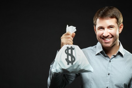 Happy young man holding money bag and looking at camera